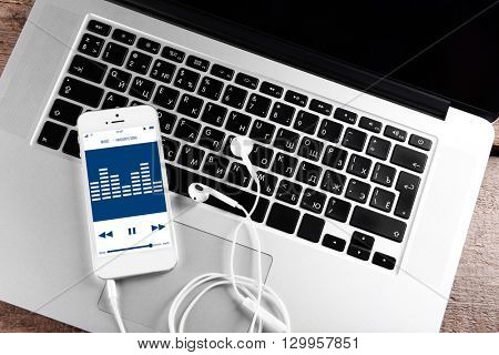 White smart phone with headphones on laptop on wooden background
