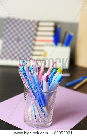 Set of colored pens in glass on black table, close up