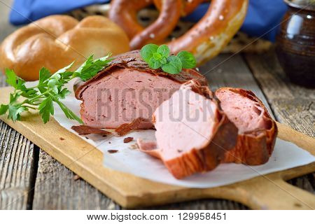 Traditional oven fresh Bavarian meat loaf with a brown crispy crust on a wooden cutting board garnished with parsley and oregano, a roll and a pretzel in the background in soft focus