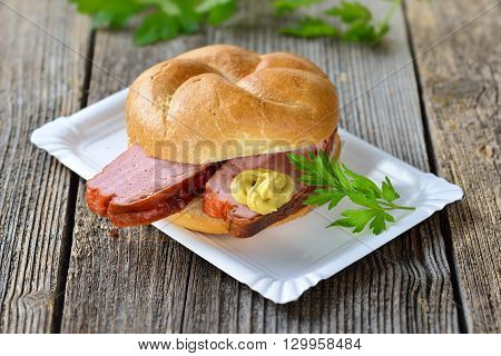 Bavarian takeaway food: A roll with baked meat loaf and mustard on a paper plate