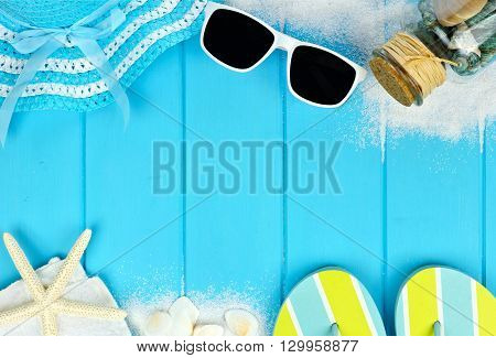 Summer double border of beach items and sea shells on blue wooden background