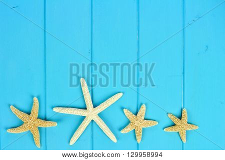 Summer bottom border of star fish on blue wooden background