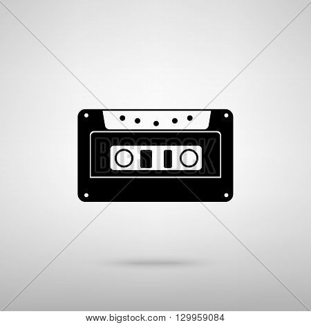 Cassette icon, audio tape sign. Black with shadow on gray.
