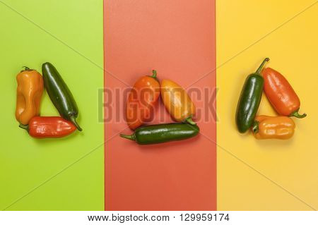 Mixture of various peppers on colored background.