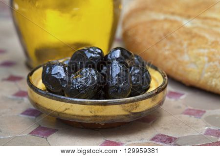 Moroccan black breakfast olives with bread and olive oil