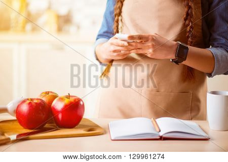 Lets cook. Pleasant woman holding cell phone and standing near table while going to cook in the kitchen