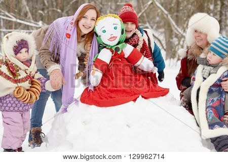 Woman and four children of different age around stuffed dummy Maslenitsa in winter park.