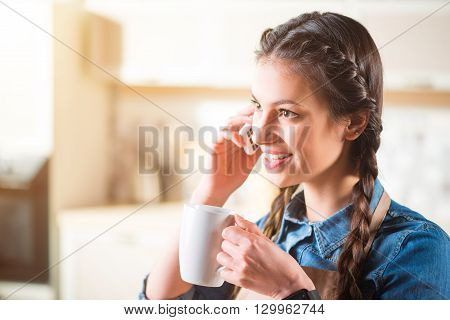 Nice to hear you. Pleasant delighted beautiful woman smiling and talking on cell phone while standing in the kitchen