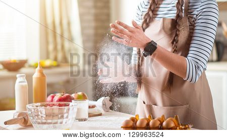Involved in process. Pleasant woman standing near table and holding flour while cooking in the kitchen