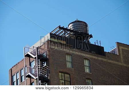 Urban water tower  and brick building against  blue sky