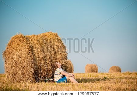 Beautiful Plus Size Young Woman In Shirt Sit Near Hay Bales In Summer Field Meadow At Blue Sly Background
