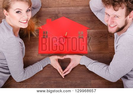 Love romance relationship home security safety concept. Couple with family symbols. Girl and boy forming heart with hands on house and keys.