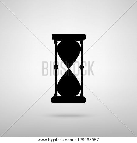 Hourglass sign. Black with shadow on gray.