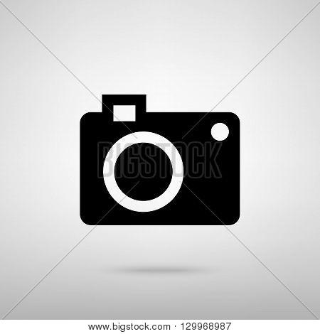 Digital camera  icon. Black with shadow on gray.