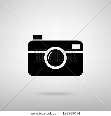 Digital photo camera icon. Black with shadow on gray.