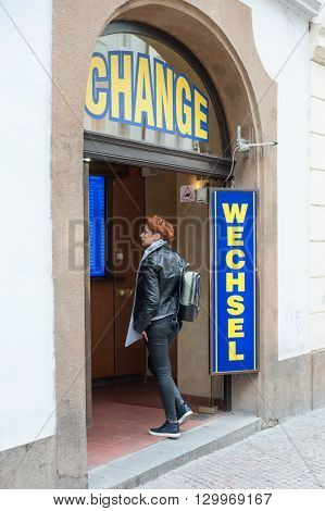 Tourist woman enter in the exchage curency office on the street