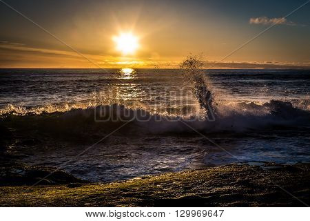 Sunset with crashing waves at Windansea Beach in La Jolla, California.