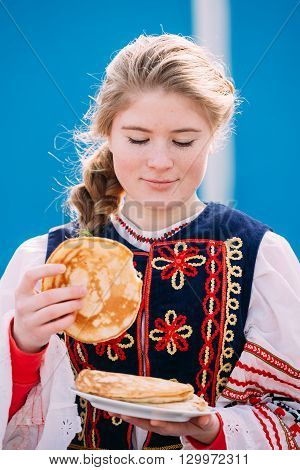 Gomel, Belarus - March 12, 2016: Unknown beautiful young woman girl in national folk clothes tries on taste  pancakes at Celebration of Maslenitsa Shrovetide holiday.