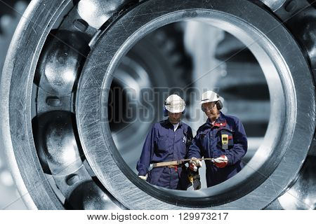two mechanics, workers standing inside giant ball-bearing, steel industrial