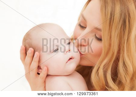 Mother holding and kissing her newborn baby. Motherhood, maternity love concept.