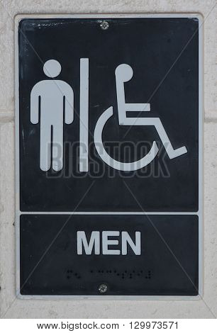 A sign for a mens bathroom posted on a brick wall