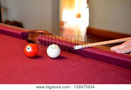 Pool billiard game in process.  Pool balls, cue stick on red felt pool table.