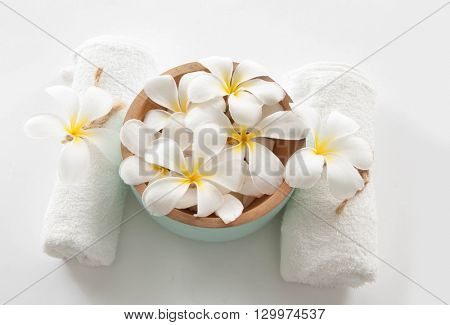 wooden bowl of white frangipani with towel