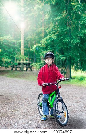 An Asian boy riding his bike in an outdoor park. Backlit by morning sunlight in background with deliberate lens flare for effect. Vertical orientation with copy space.