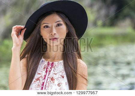 Outdoor portrait of a beautiful thoughtful young Chinese Asian young woman or girl wearing a summer dress and a black hat