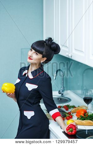 Young slim girl in the kitchen. Girl chooses vegetables for dinner. Girl dreaming. Household chores .