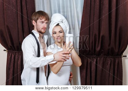 Husband and wife make selfie. Girl with a towel over his head. A man in an unbuttoned shirt and tie.