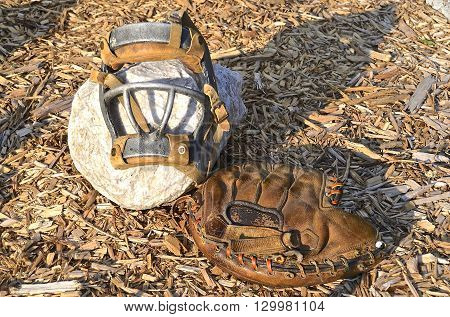 An old catchers mitt and face mask represent the game of baseball from an era ago.