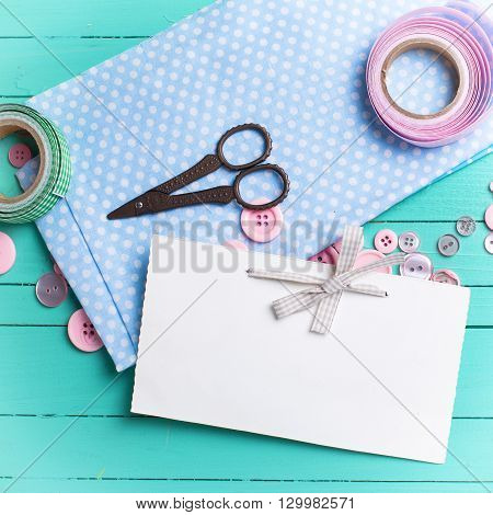 Sewing thread - buttons scissors fabric and empty tag on turquoise wooden background. Selective focus. Scrapbboking. Flat lay. Place for text. Toned image.