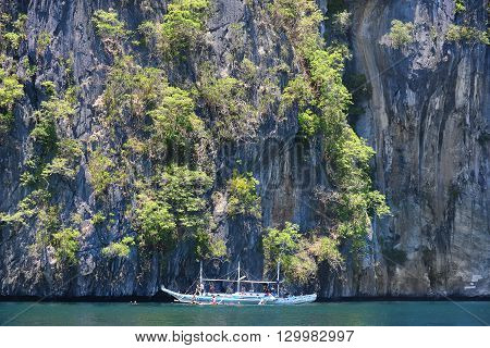 EL NIDO PALAWAN PHILIPPINES - APRIL 5 2016: Pleasure boat with tourists swimming in the waters off of El Nido Island in the Philippines.