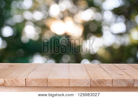 brown wood table top on bokeh abstract green background - can be used for montage or display your products