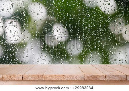 brown wood table top on bokeh abstract water drop background - can be used for montage or display your products