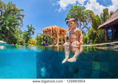 Funny underwater photo of little baby and dog swim in blue outdoor swimming pool. Children water sports activity and swimming lessons training dogs fun games with family pet on summer beach holiday.