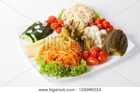 Different marinated vegetables served on a white plate