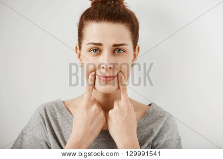 Close Up Shot Of Beautiful Teenage Girl Forcing A Smile, Holding Her Fingers At The Edges Of Her Lip