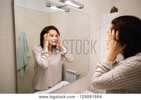 Portrait Of Attractive Middle-aged Asian Female Examining Her Skin For Wrinkles, Holding Her Face, L