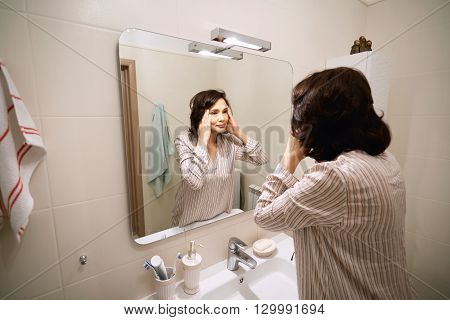 Attractive Mature Asian Woman With Dark Hair, Wearing Night-suit, Looking At Her Reflection In The M