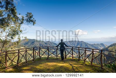 Woman looking at mountain landscape from Santo da Serra park viewpoint. Madeira island, Portugal.