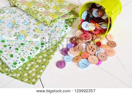Pieces of fabric, set multi-colored buttons in a small decorative bucket. Sewing concept