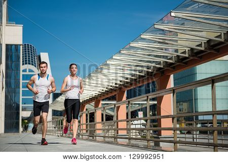Young sport couple jogging together in city environment