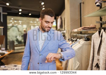 sale, shopping, fashion, style and people concept - happy young man in jacket looking at wristwatch at clothing store