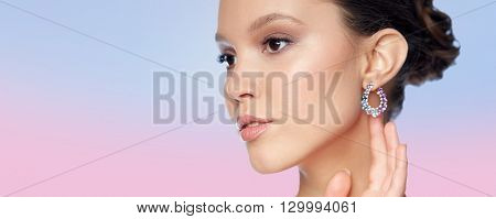 beauty, jewelry, accessories, people and luxury concept - close up of beautiful asian woman face with earring over rose quartz and serenity gradient background