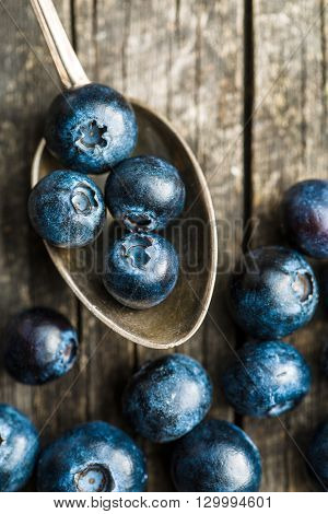 Tasty blueberries fruit in silver spoon. Blueberries are antioxidant organic superfood. Top view.