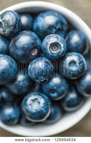Tasty blueberries fruit in bowl. Blueberries are antioxidant organic superfood. Top view.