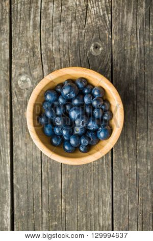 Tasty blueberries fruit in wooden bowl. Blueberries are antioxidant organic superfood. Top view.