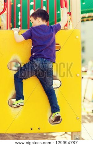 summer, childhood, leisure and people concept - happy little boy on children playground climbing frame from back